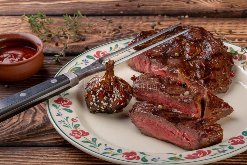 Carne arrostita fresca Raro di medium arrostito della bistecca di manzo su fondo di legno fotografia stock