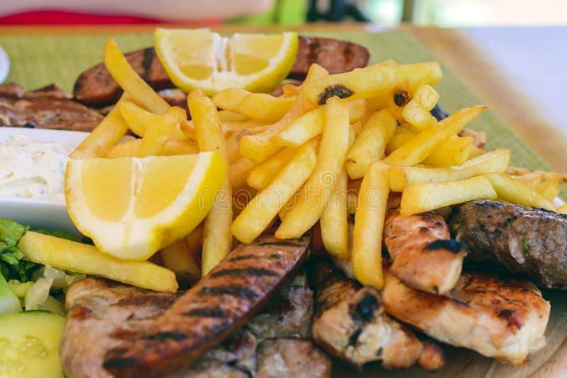 Carne arrostita mista e verdure - carne arrostita mista e salsiccie sul bordo di legno Il pasto delizioso assortito con la patata immagine stock