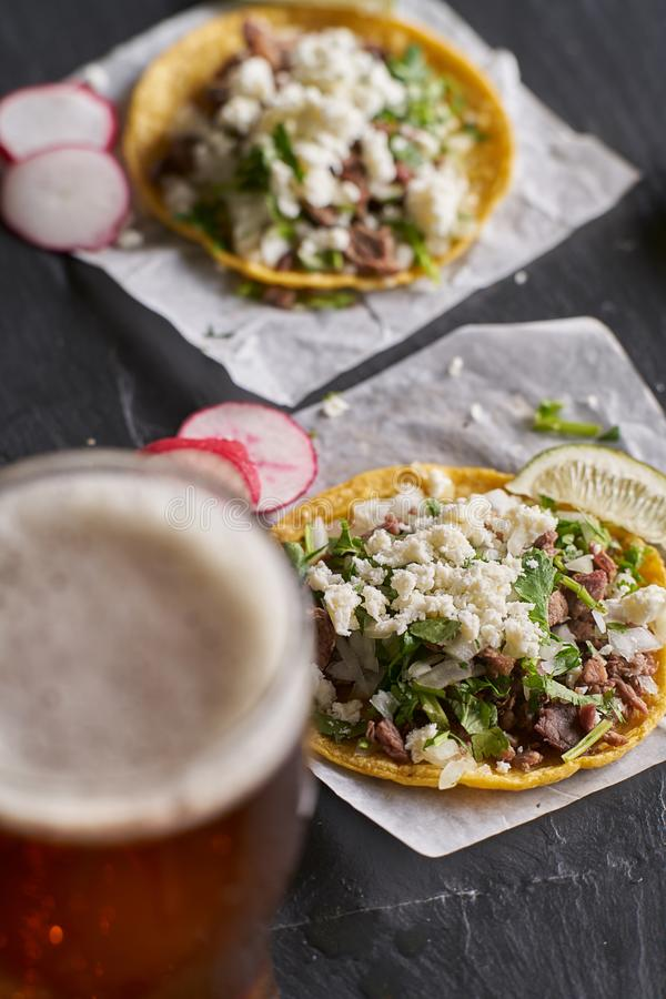 Carne asada beef tacos with queso fresco and beer. With selective focus royalty free stock photos