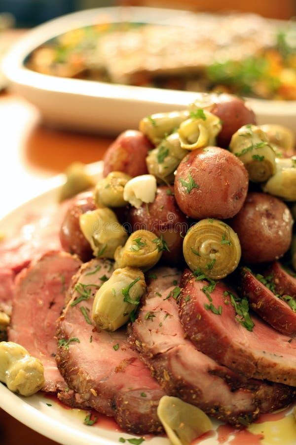 Carne asada de cerdo con las patatas y los corazones de alcachofa imagen de archivo