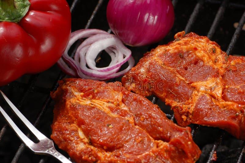 Carne asada a la parilla con la cebolla y la pimienta imagenes de archivo