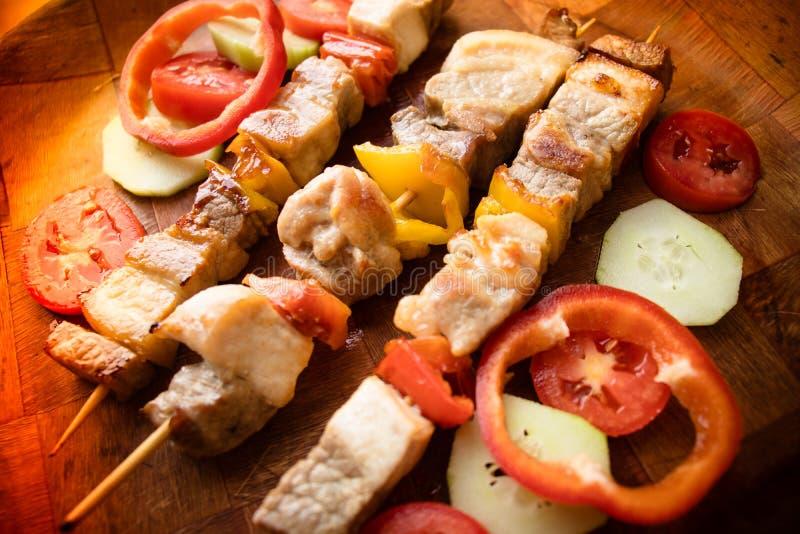 Carne asada a la parilla con los vehículos Kebab o shashlik asado a la parilla en los palillos fotografía de archivo