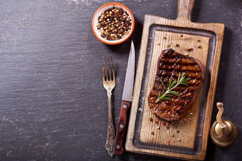 Carne asada a la parrilla con romero en el tablero de madera imagen de archivo libre de regalías