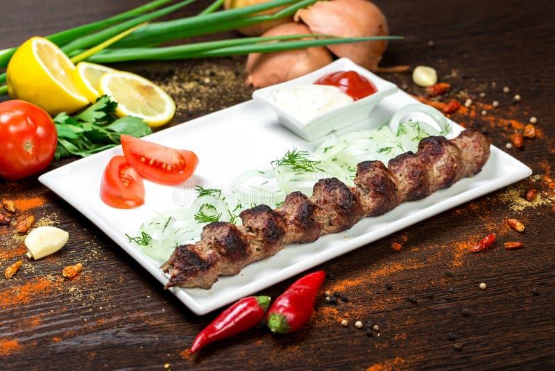 Carne asada a la parrilla deliciosa clasificada con la verdura sobre los carbones en una barbacoa foto de archivo