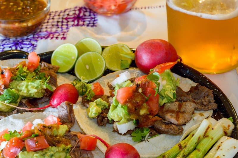 Carne asada tacos with craft beer and condiments in Tijuana with copy space. Carne asada tacos with craft beer, lime, radish, scallions and condiments in Tijuana stock photos