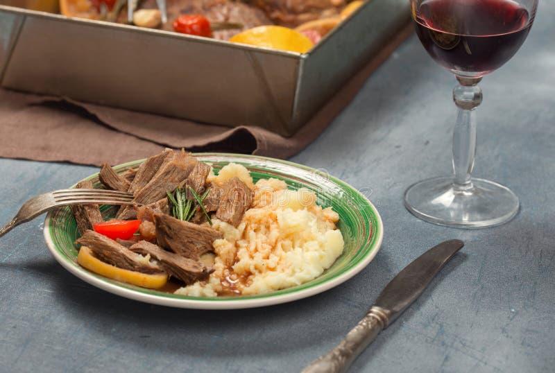 Carne assada com batatas e vidro triturados do vinho tinto fotografia de stock royalty free