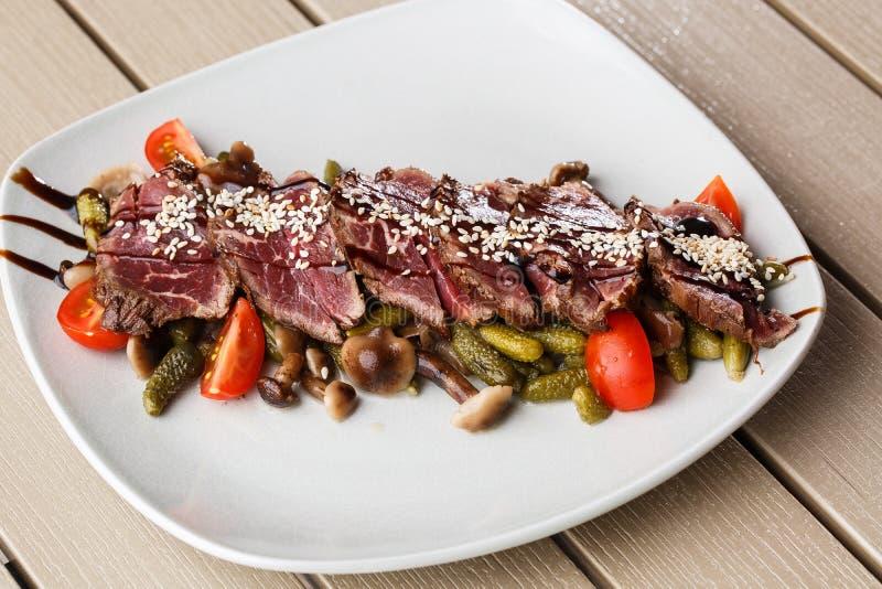 Carne assada rara média cortada com salmouras, tomates de cereja, cogumelos em uma placa branca no fundo de madeira foto de stock royalty free
