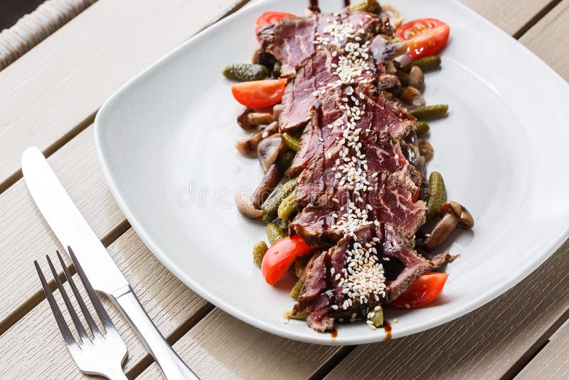 Carne assada rara média cortada com salmouras, tomates de cereja, cogumelos em uma placa branca no fundo de madeira imagem de stock