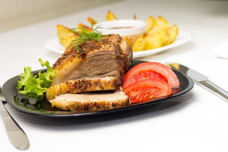 Carne cocida con la patata asada a la parrilla en la tabla blanca fotos de archivo