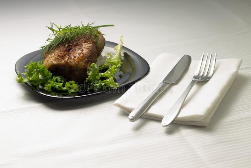 Carne cocida en la tabla servida con el mantel blanco foto de archivo libre de regalías