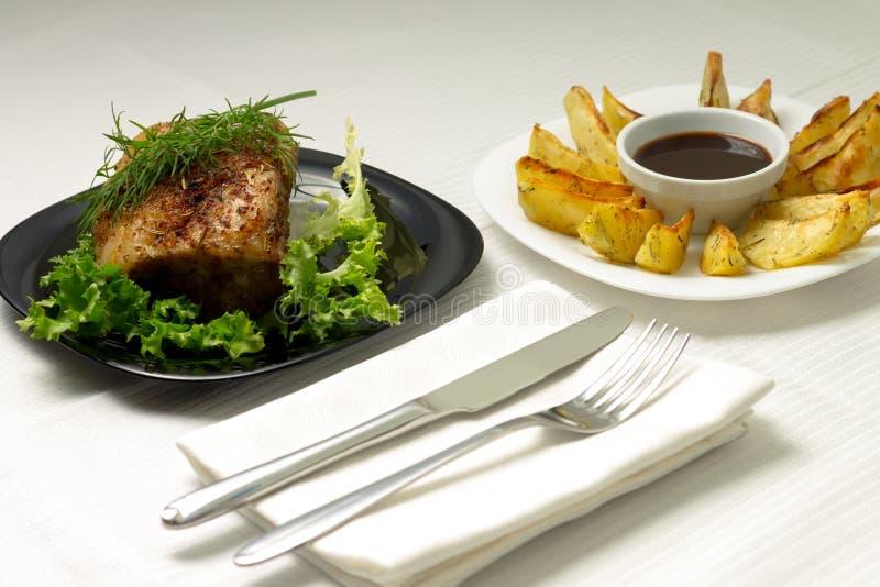 Carne cocida en la tabla servida con el mantel blanco imágenes de archivo libres de regalías