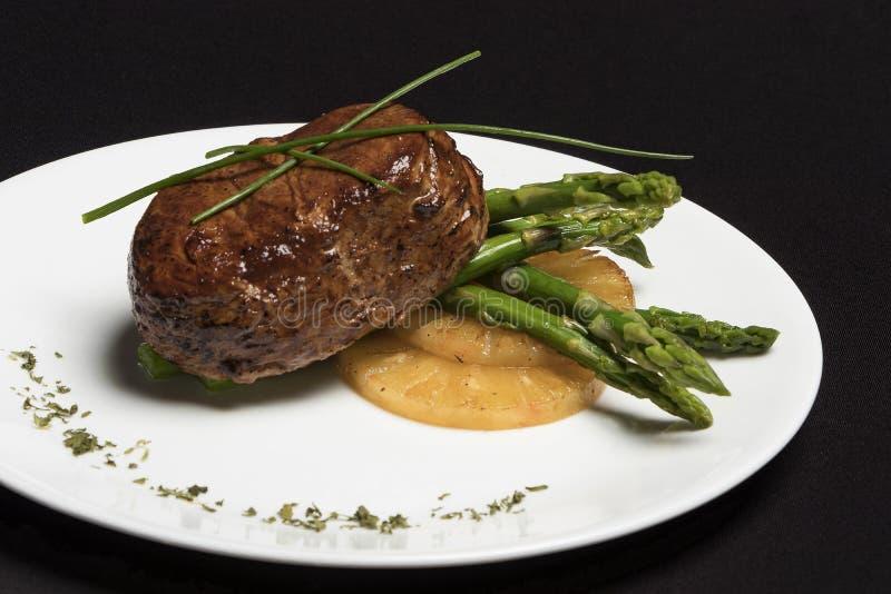 Carne com aspargo e abacaxi na placa branca e no fundo preto imagens de stock