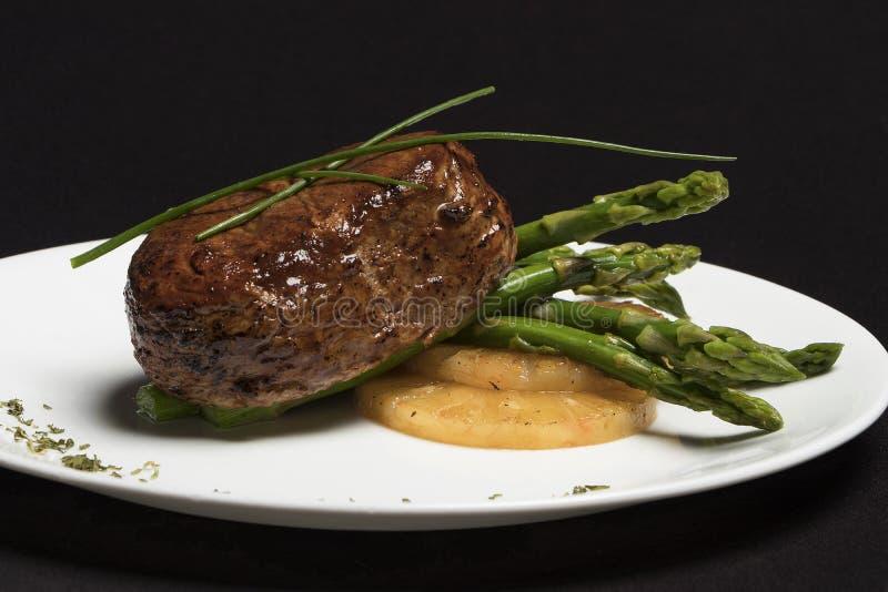 Carne com aspargo e abacaxi na placa branca e no fundo preto fotos de stock royalty free