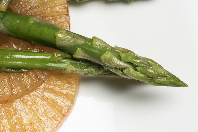 Carne com aspargo e abacaxi na placa branca e no fundo preto fotografia de stock royalty free