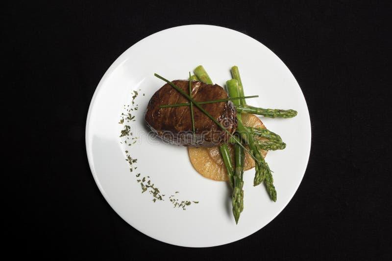 Carne com aspargo e abacaxi na placa branca e no fundo preto imagem de stock