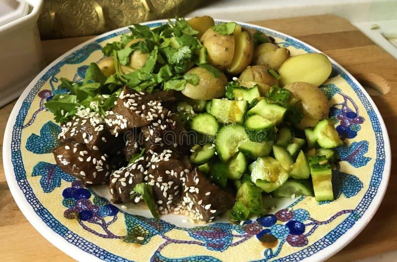 Carne com batatas e pepinos na placa fotografia de stock royalty free