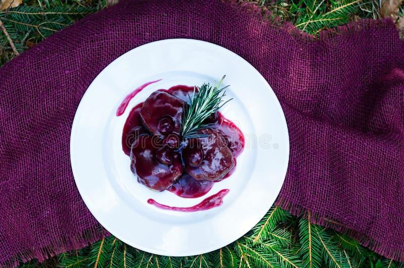 Carne com molho do agridoce em uma placa branca e em um guardanapo carmesim, em um fundo natural do abeto vermelho foto de stock royalty free