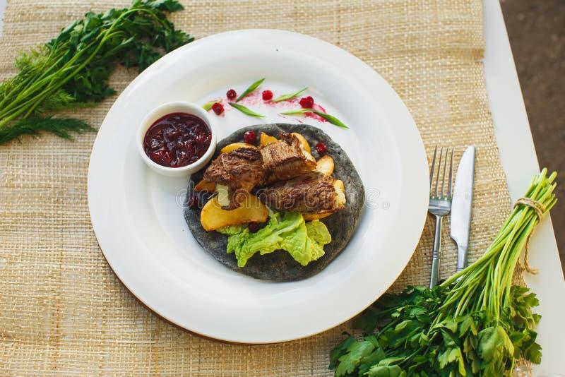 Carne com verdes em um bolo o fundo da natureza Piquenique fotografia de stock