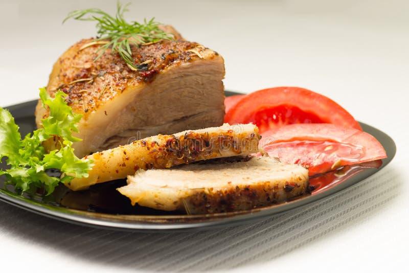 Carne cortada cocida en plato negro foto de archivo