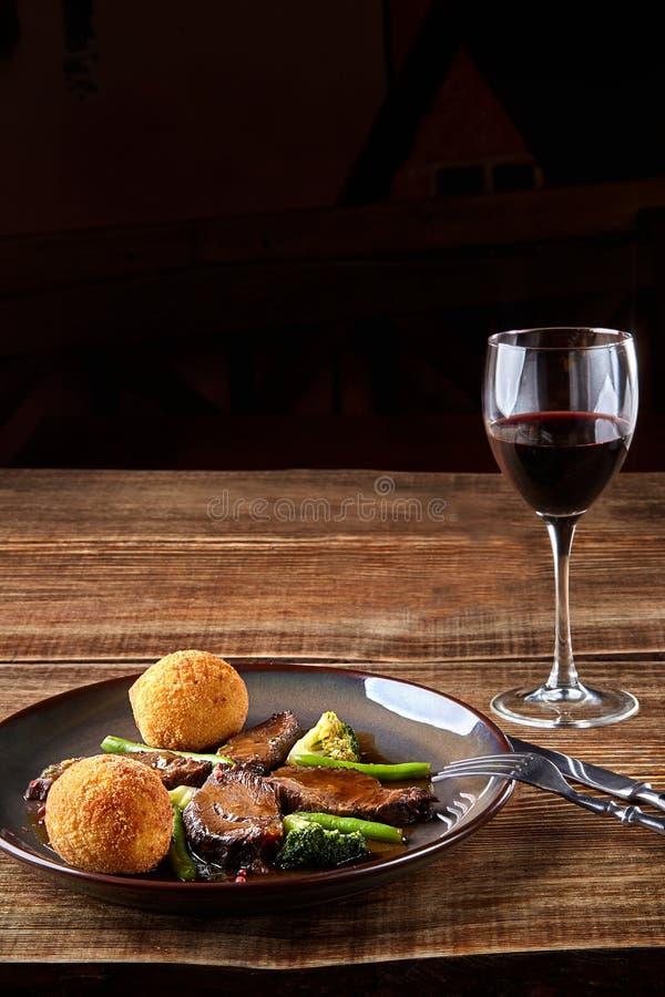 Carne cozido com vegetais e um vidro do vinho seco vermelho na tabela de madeira, fim acima Pratos quentes da carne fotografia de stock royalty free