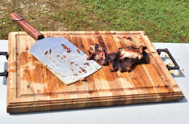 Carne crepitante cortada Smoked do assado do BBQ apenas fora da grade na placa de corte de madeira imagens de stock