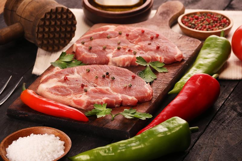 Carne crua Bife cru da carne de porco em uma placa de corte com vegetais, pimentas, tomate, sal e especiarias em um fundo preto fotografia de stock