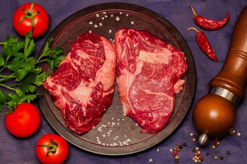 Carne crua Bife em uma placa de corte redonda com tomates, salsa e especiarias fotos de stock