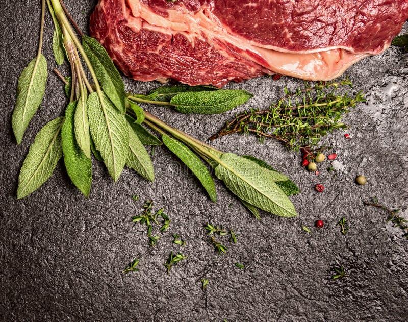 Carne crua da carne com as ervas frescas do sábio e do tomilho no fundo de pedra preto, vista superior fotografia de stock royalty free