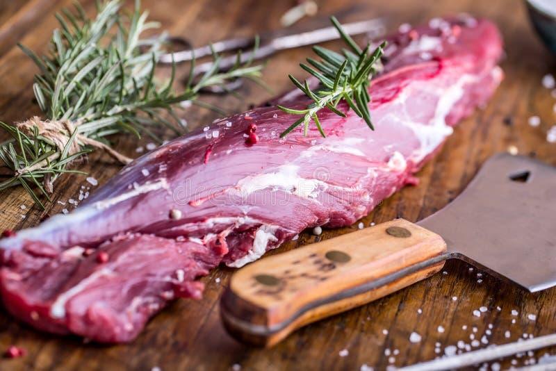 Carne crua da carne O bife cru do lombinho de carne em uma placa de corte com alecrins salpica o sal em outras posições fotografia de stock