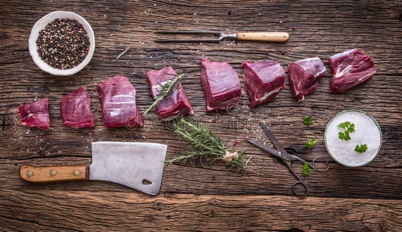 Carne crua da carne O bife cru do lombinho de carne em uma placa de corte com alecrins salpica o sal em outras posições fotografia de stock royalty free