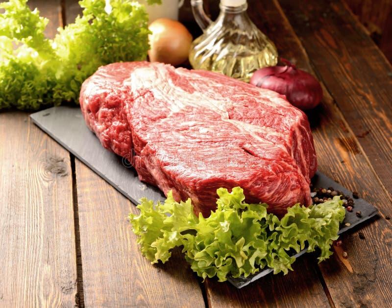 Carne crua de mármore em uma placa, em cebolas, em salada e e em especiarias do basalto em um fundo de madeira fotos de stock royalty free