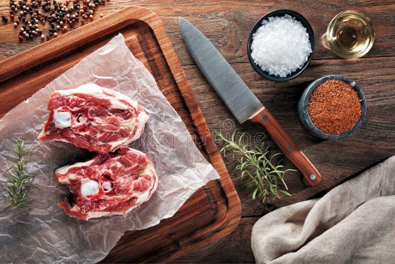 Carne crua do pescoço do cordeiro no papel de cozimento branco e na tabela de corte de madeira fotografia de stock