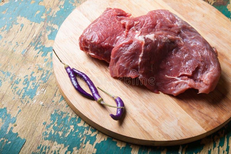 Carne crua fresca na placa de corte leve em uma tabela de madeira velha Em fotografia de stock royalty free