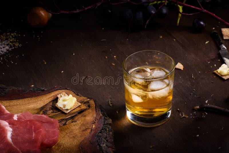 Carne cruda, bistecca di manzo sulla tavola di legno, un vetro di whiskey fotografia stock libera da diritti