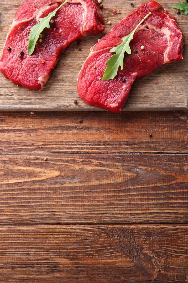 Carne cruda con las especias y el arugula en fondo de madera foto de archivo libre de regalías