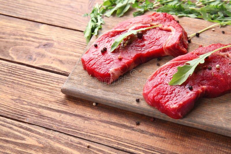 Carne cruda con las especias y el arugula en fondo de madera imagen de archivo libre de regalías