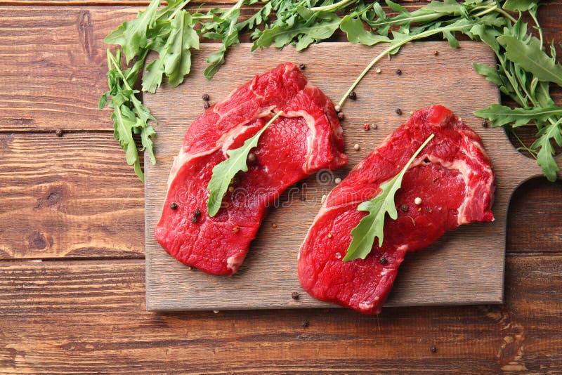 Carne cruda con las especias y el arugula en fondo de madera imagen de archivo
