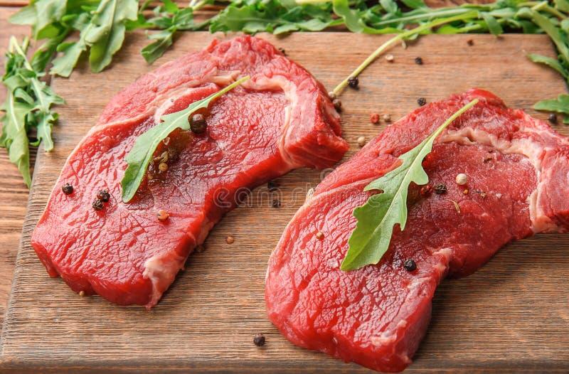 Carne cruda con las especias y el arugula en el tablero de madera fotografía de archivo