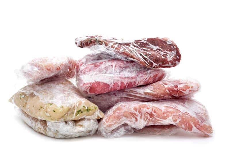 Carne cruda congelada envuelta de plástico foto de archivo