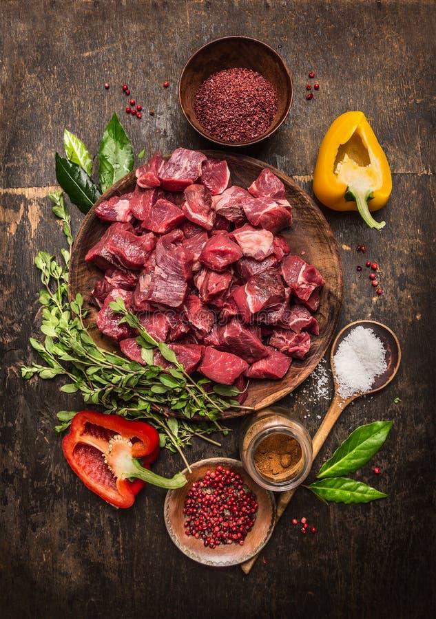 Carne cruda cruda affettata in cubi con le erbe, le verdure e le spezie fresche su fondo di legno rustico, ingredienti per lo stu fotografie stock