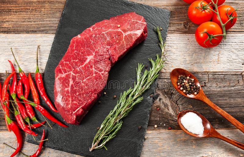 Carne cruda, carne de vaca con las especias para cocinar en tablero negro imagenes de archivo