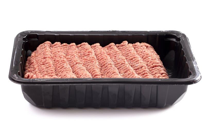 Carne cruda dell'hamburger in un pacchetto di plastica su un fondo bianco fotografia stock libera da diritti
