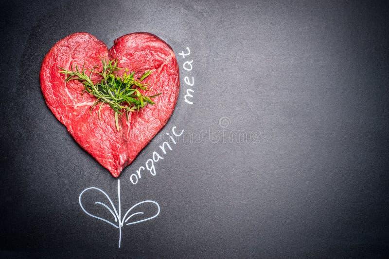 Carne cruda di forma del cuore con le erbe con l'iscrizione organica dipinta della carne intorno Fondo scuro della lavagna fotografia stock libera da diritti