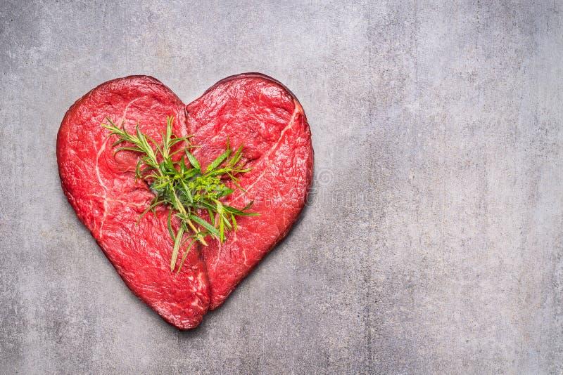 Carne cruda di forma del cuore con le erbe ed il testo su fondo concreto grigio, vista superiore immagine stock