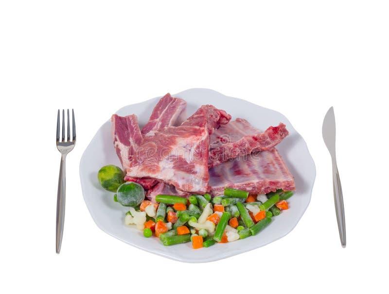 Carne cruda e verdure su un piatto immagini stock libere da diritti
