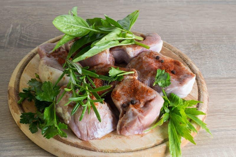 Carne cruda en un plato de madera con hierba verde foto de archivo