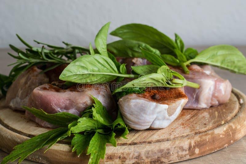 Carne cruda en un plato de madera con hierba verde fotos de archivo