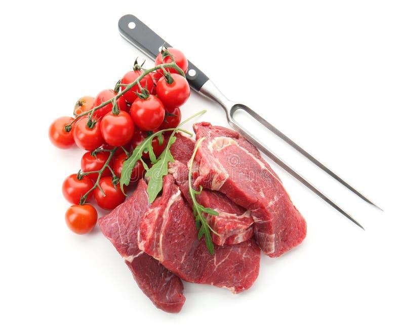 Carne cruda fresca con la bifurcación, el arugula y tomates en el fondo blanco foto de archivo libre de regalías