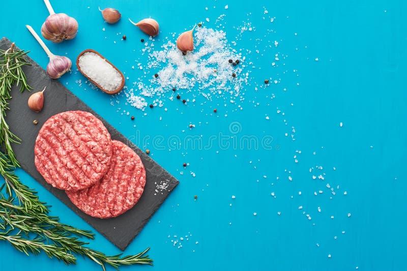 Carne cruda fresca de la carne de vaca con las hierbas y la sal en fondo de la turquesa fotografía de archivo libre de regalías