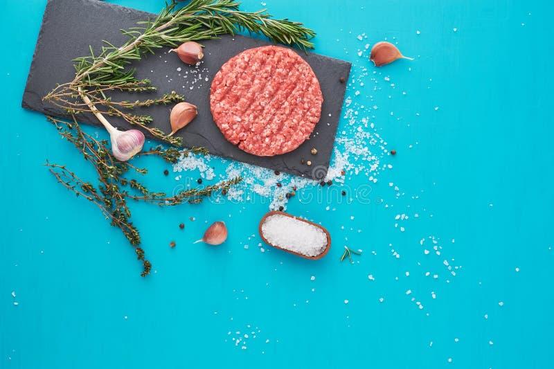 Carne cruda fresca de la carne de vaca con las hierbas y la sal en fondo de la turquesa fotos de archivo libres de regalías